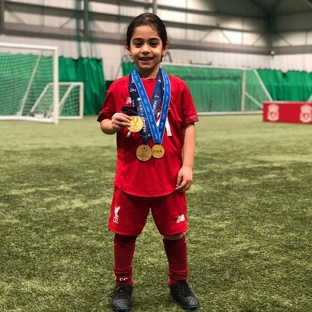 Arat wearing some medals which Juger klopp and his players get for Liverpool fc .,